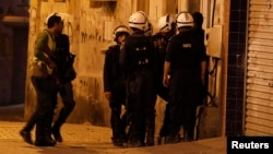 Bahraini riot police enter a house during a raid to arrest suspected protesters involved in clashes (file photo).