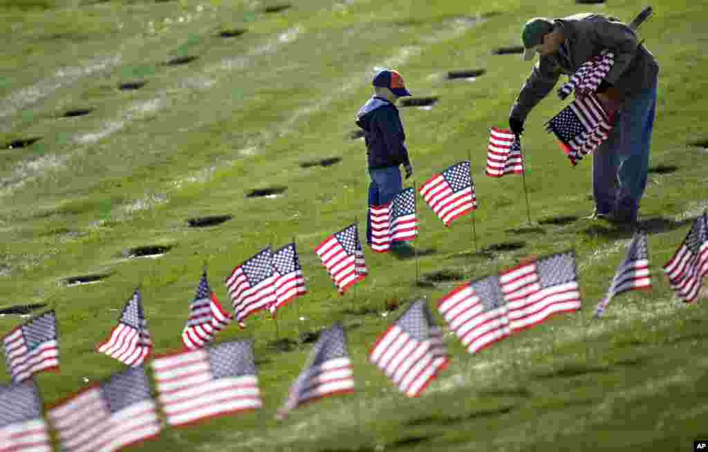 Joseph Manning, right, of Raynham, Mass., and his son Joey, 6, a Cub Scout, place U.S. flags at the graves of deceased veterans at the National Cemetery in Bourne, Mass., Nov. 10, 2012. (AP)