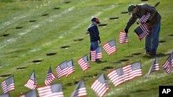 麻省的曼宁父子在麻省国家陵墓为阵亡将士墓地插美国国旗