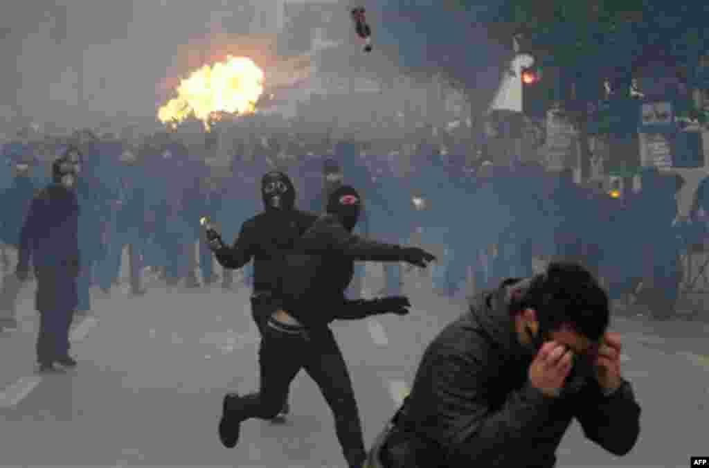 Protesters throw petrol bombs during clashes in Athens, Wednesday, Dec. 15, 2010. Hundreds of protesters clashed with riot police across central Athens Wednesday, smashing cars and hurling gasoline bombs during a massive labor protest against the governme