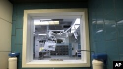 FILE - An operating room is seen through a window at a sanitizing station in New Orleans.