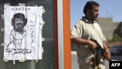 Binh sĩ của phe nổi dậy Libya đứng cạnh hình vẽ nhà độc tài đang bỏ trốn Moammar Gadhafi tại một chốt kiểm soát ở Tripoli