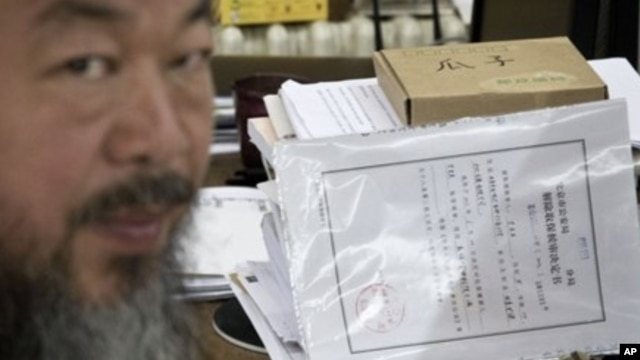 Artist Ai Weiwei with notice from city's Chaoyang District police that restrictions would expire Friday, Beijing, June 21, 2012.