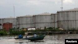 FILE - A boat travels down a river near the southeastern oil city of Warri, in Delta state, Nigeria, June 18, 2017.