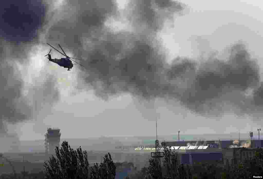 A Ukrainian helicopter Mi-24 gunship fires its cannons against rebels at the main terminal building at the airport in Donetsk, Ukraine, May 26, 2014.