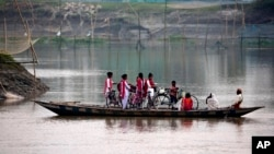 School children ride on a boat with their bicycles to cross the river Brahmaputra in Kasoshila village on the outskirts of Gauhati, India, Monday, Oct. 21, 2019.