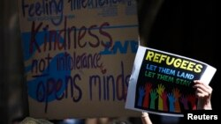 FILE - Protesters hold placards at the 'Stand up for Refugees' rally held in central Sydney. Protesters set fires at an Australian-run detention center on Christmas Island following the death of an Iranian-born asylum seeker.