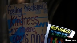 FILE - Protesters hold placards at a Stand up for Refugees rally in central Sydney, Oct. 11, 2014. For at least a year, demonstrators have demanded changes to the Australian government's tough policies on granting asylum.