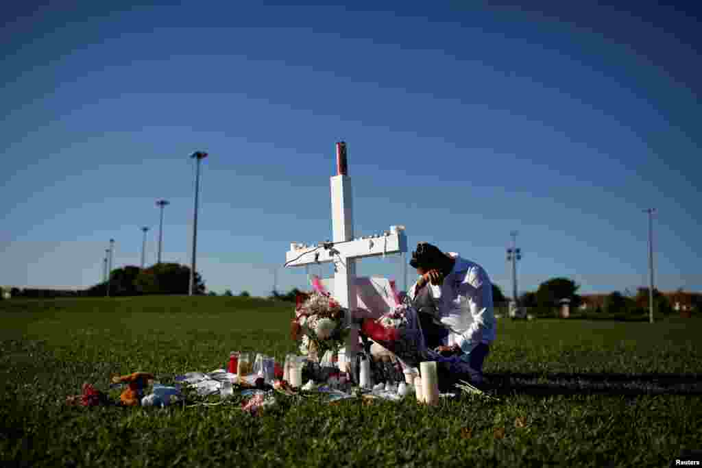 Joe Zevuloni mourns in front of a cross placed in a park to commemorate the victims of the shooting at Marjory Stoneman Douglas High School, in Parkland, Florida, U.S.