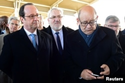 French President Francois Hollande (L) and French Minister for Defence Jean-Yves Le Drian (R) visit French Forces at the Air Force Base 118 in Mont-de-Marsan, France, Jan. 6, 2017.