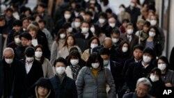 18일 일본 도쿄에서 시민들이 마스크를 착용한 채 출근하고 있다.