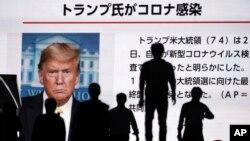 Người dân Nhật đi ngang qua một màn ảnh truyền hình tại Tokyo loan tin Tổng thống Donald Trump xét nghiệm dương tính với virus corona, ngày 2/10/2020.