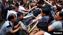 Những người chống phong trào Chiếm Trung (trái) tìm cách dẹp bỏ rào chắn của người biểu tình ủng hộ dân chủ trên đường phố ở khu Mongmok, ngày 4 tháng 10, 2014.