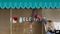 Žena pere izlog pred ponovno otvarane prodavnice u centru Beograda, pred ukidanje vanrednog stanja u Srbiji, 4. maja 2020.