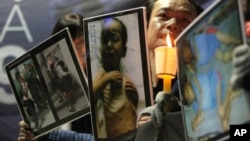 South Korean Christians hold pictures of what they claim are North Korean children suffering from famine and North Korean defectors while participating in a rally denouncing alleged human rights violations against North Koreans, in Seoul, South Korea.