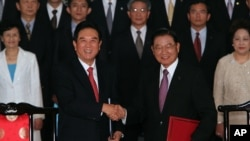 Chen Yunlin, left, shakes hands with Chiang Pin-kung, after signing investment protection pact, Taipei, Taiwan, August 9, 2012.