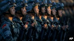 Soldiers of China's People Liberation Army (PLA) stand in line in front of Tiananmen Gate in Beijing as they prepare to march in a military parade to observe the 70th anniversary of the end of World War II in Beijing Thursday Sept. 3, 2015. (Jason Lee/Pool Photo via AP)