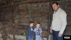 Branko Čukanić sa sinom Damjanom i komšijinim sinom u svojoj štali, gde se nalazila ukradena krava (Foto: VOA)