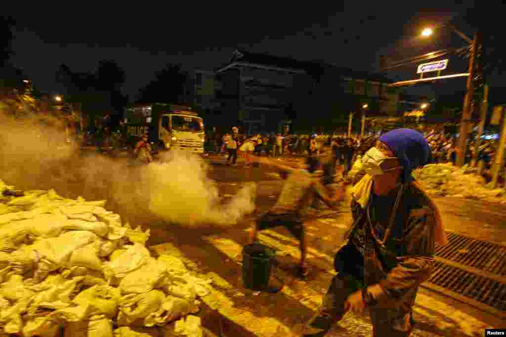 An anti-government protester throws a tear gas canister towards police from behind a barricade during clashes near the Government House in Bangkok, Dec. 1, 2013.