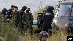 Soldiers stand guard as federal police officers carry a stretcher with the body of a victim of a helicopter crash in which Mexico's Interior Minister Francisco Blake Mora and seven others were killed near Mexico City, November 11, 2011.