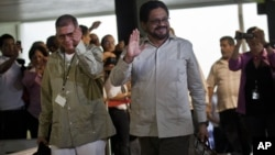 Ivan Marquez, right, and Ricardo Tellez, members of the negotiation team for Colombia's Revolutionary Armed Forces of Colombia, or FARC, wave as they arrive for peace talks in Havana, Cuba, Monday, Nov. 19, 2012.