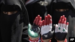 Yemeni female protesters show their hands with colors of the pre-Gadhafi Libya, Yemen and Syria flags during a demonstration demanding the resignation of Yemeni President Ali Abdullah Saleh in Sana'a, Yemen, October 21, 2011.