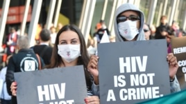 Activists display placards during a rally at the AIDS Conference 2014 at the Melbourne Convention and Exhibition Centre (MCEC) in Melbourne, on July 22, 2014.