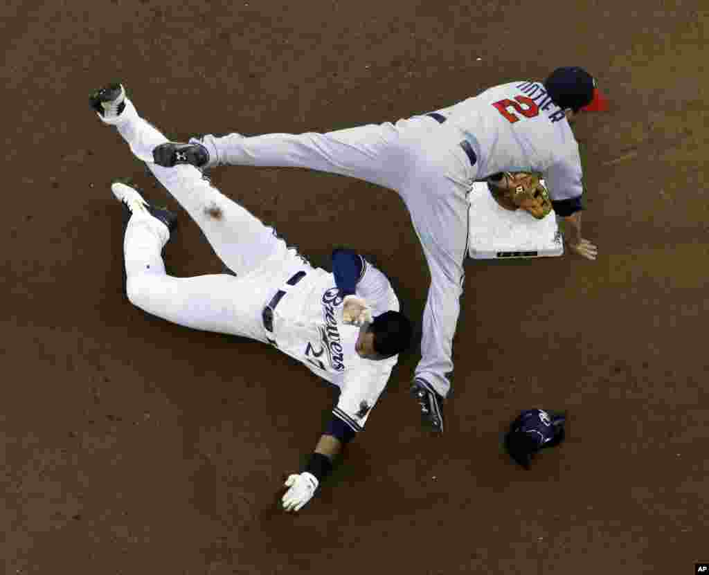 Minnesota Twins' Brian Dozier (2) leaps over Milwaukee Brewers' Carlos Gomez (27) at second base to turn a double play on a ball hit by Khris Davis during the fourth inning of a baseball game in Milwaukee, Wisconsin, USA, June 2, 2014.