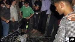 Warga Palestina berkerumun di dekat sepeda motor yang hancur akibat serangan udara Israel di Jabalia, Jalur Gaza utara (13/10).