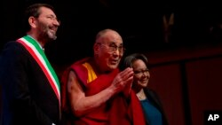 Tibetan spiritual leader the Dalai Lama (C), flanked on left by Rome's Mayor Ignazio Marino, arrives at the opening of the World Summit of Nobel Peace Laureates in Rome, Dec. 12, 2014.