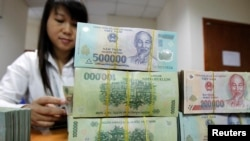 An employee counts Vietnamese dong banknotes at a counter of the Vietnam International Bank in Hanoi November 3, 2011. REUTERS/Kham (VIETNAM - Tags: BUSINESS)
