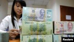 Nhân viên ngân hàng đếm tiền tại quầy giao dịch của Ngân hàng Quốc tế Việt Nam tại Hà Nội.