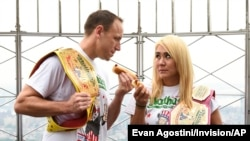 Defending men's champion Joey Chestnut, left, and defending women's champion Miki Sudo pose together during Nathan's Famous international Fourth of July hot dog eating in New York City, in 2019.