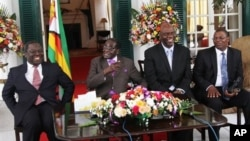 From left, Prime Minister Morgan Tsvangirai, President Robert Mugabe and other Zimbabwean officials address a press conference at the State House, Harare, Jan. 17, 2013.