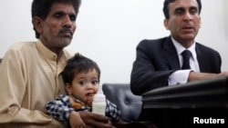 Nine-month-old baby Musa Khan sits on his grandfather's lap before appearing in a court in Lahore, April 12, 2014.