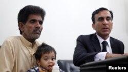 Bé Musa Khan 9 tháng tuổi được người ông bế ra tòa ở Lahore, ngày 12/4/2014.