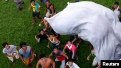 Para penyintas Topan Haiyan menunggu karung berisi bantuan pangan dijatuhkan dari helikopter angkatan udara Filipina di Tolosa, provinsi Leyte di Filipina tengah (21/11). (Reuters/Erik De Castro)