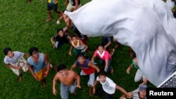 Survivors of Typhoon Haiyan wait for a sack containing food supplies to drop from a Philippine Air Force helicopter in Tolosa, Leyte in central Philippines Nov. 21, 2013.