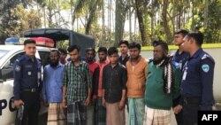 Polisi Bangladesh bersama tersangka penyelundupan manusia, di Teknaf, 13 Februari 2020. (Foto: AFP)