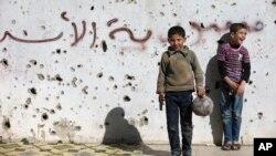 """Un niño sirio sostiene una pistola de juguete mientras juega al fútbol con otros entre edificios destruidos en lo que un graffiti dice """"Siria al-Assad"""" en la ciudad vieja de Homs, Siria, el viernes, 26 de febrero de 2016."""