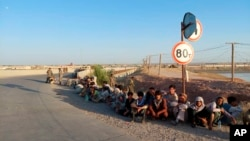 塔吉克斯坦邊防部隊公佈的照片顯示阿富汗政府士兵坐在塔吉克斯坦-阿富汗邊境線附近塔吉克斯坦境內的一座橋樑附近。 (2021年6月22日)