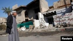 2013年12月15日一名男子站在巴格达汽车炸弹袭击现场附近(资料照片)