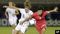 지난 2012년 일본 도쿄에서 열린 20세 이하 여자월드컵 8강전에서 북한의 전명화 선수가 미국의 모건 브라이언 선수(왼쪽)와 공을 다투고 있는 있다.