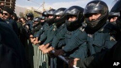 Iranian police officers protect the Saudi Arabian Embassy during a gathering of protesters blaming the Arab country for a deadly stampede that killed more than 700 pilgrims, in Tehran, Iran, Sept. 27, 2015.