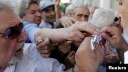 Пенсионеры разбирают купоны, на получение части своей пенсии в филиал Национального банка в Афинах, Греция, 6 июля 2015.