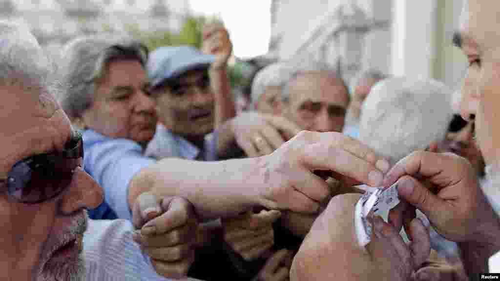 Des retraités recevant en priorité des tickets pour recevoir une partie de leurs pensions, devant la Banque nationale à Athènes, en Grèce
