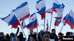Spectators watch the action standing next to Russian and Crimean flags during celebrations marking the first anniversary of Russia's annexation of Ukraine's Black Sea peninsula of Crimea, in central Simferopol, March 16, 2015.
