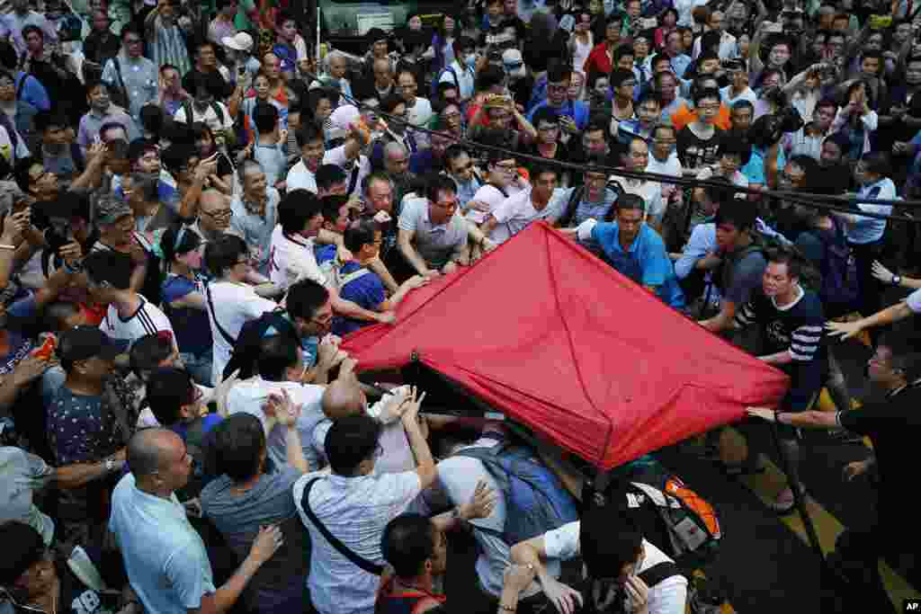 Residents and pro-Beijing supporters tear down a pro-democracy activist tent in Mong Kok district, Oct. 3, 2014.
