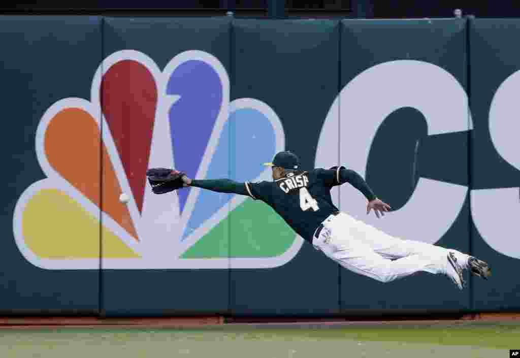 កីឡាករ Coco Crisp របស់ក្រុម Oakland Athletics ហក់ចាប់បាល់របស់កីឡាករ Luis Valbuena របស់ក្រុម Houston Astros ក្នុងតង់ទី២នៃការប្រកួតបាល់ម្យ៉ាងដែលគេហៅថា Baseball កាលពីថ្ងៃទី១៨ ខែកក្កដា ឆ្នាំ២០១៦។