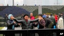 Giới chức chính phủ Trung Quốc kéo tay một thân nhân đang bày tỏ sự đau buồn tại hiện trường ở trung tâm Thượng Hải, ngày 6/1/2015.